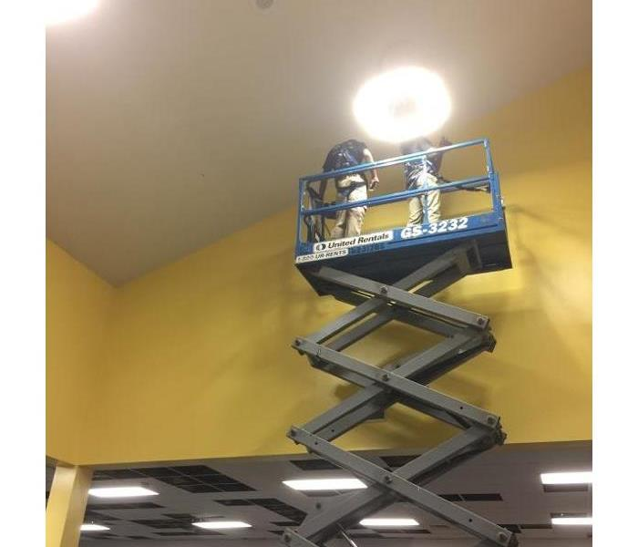 2 employees on a lift next to a yellow wall