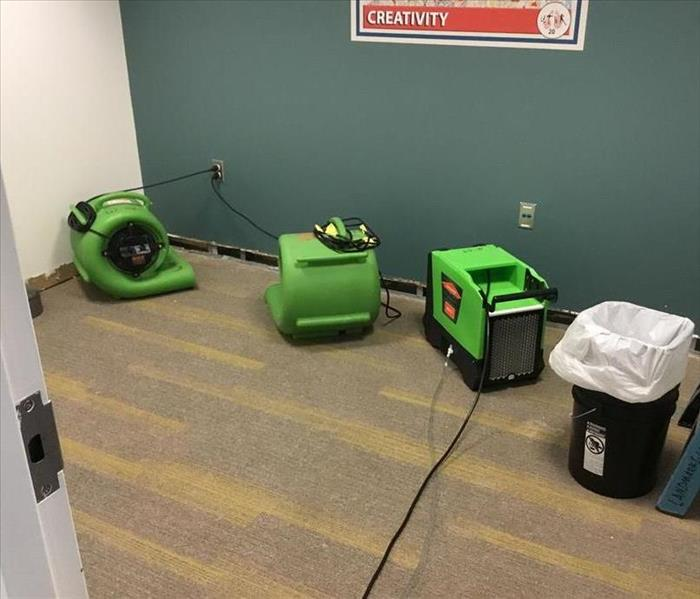 commercial office with wet carpets and baseboards removed with high powered fans set in proper placement for drying.