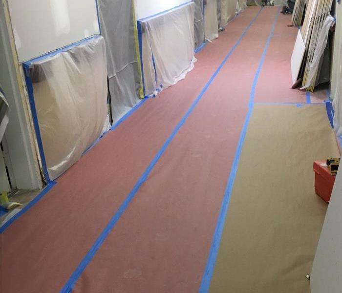 A hallway with blue tape and plastic covering.