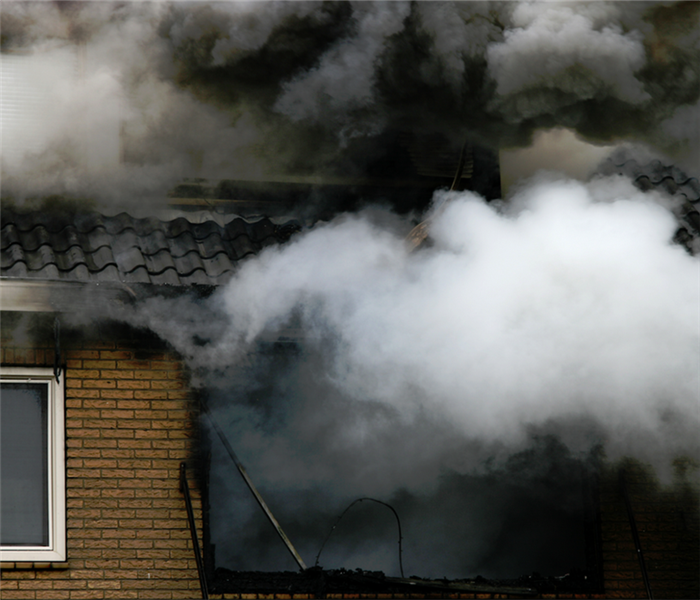 smoke billowing from the windows of a house